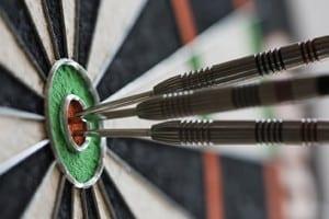 Darts hitting bull's eye on the dartboard
